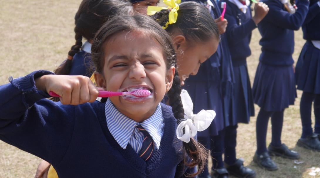 Una niña se lava los dientes después de un taller sobre higiene en nuestro voluntariado social en Nepal.
